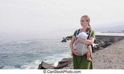 A young mother is travelling on the beach with her baby in a sling
