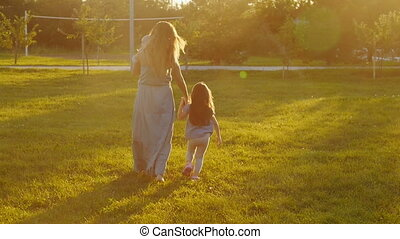 A young mother is walking in the park at sunset