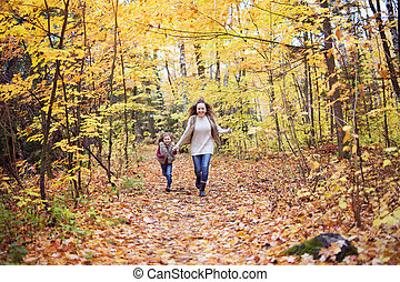 Young mother playing with her daughter in autumn park
