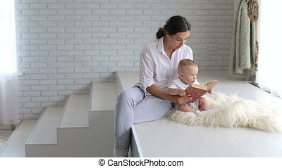 A young mother reads a book to her newborn child in a modern apartment.