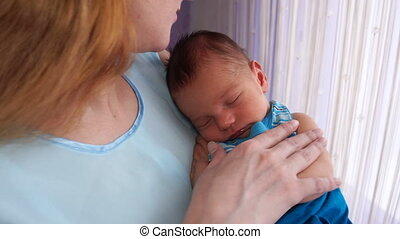 A young mother rocking a newborn in her arms.