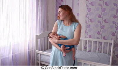A young mother rocking a newborn in her arms