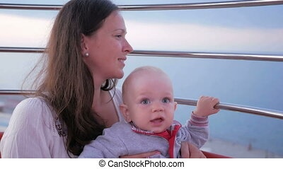A young mother shows her son a beautiful city with a Ferris wheel height. Kid inspects all around. The boy is 1 year.