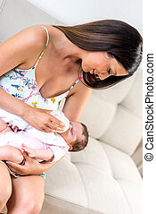 A young mother sitting on a sofa and feeding her baby