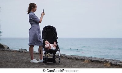 A young mother stands with a baby sitting in a wheelchair near the ocean and takes pictures on a smartphone beautiful photos for social networks and blog