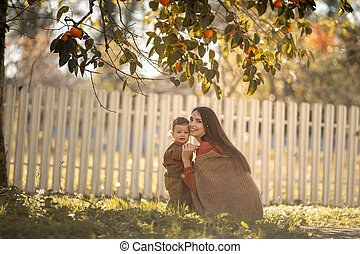 A young mother walks with her son in the garden with ripe orange trees