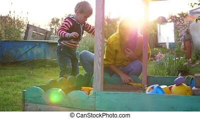 a young mother with a child playing in the sandbox. Summer day, sun rays on the Playground