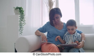 A young mother with a child reading a book sitting in a bright white interior of the house in the living room on the couch.