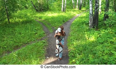 A young mother with a child walking in the Park. Mom holds...