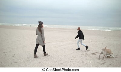 A young mother with a teenager daughter and a dog are happy to walk along the beach.