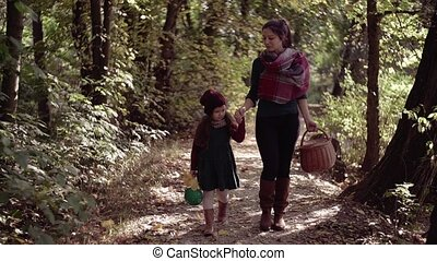 A young mother with a toddler daughter walking in forest in...