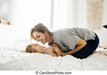Young mother with her little son relaxing and playing in the bed at the weekend together