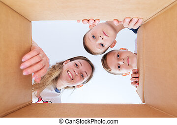A young mother with her sons looks into the box.