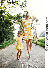 A young mother with small daughter playing hopscotch on a road in summer.