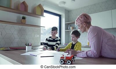 A young mother with two children drawing in a kitchen. - A...