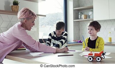 A young mother with two children drawing in a kitchen.