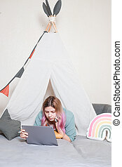 A young mother works on a tablet computer at home, in a children's hut made of sheets. concept of quarantine