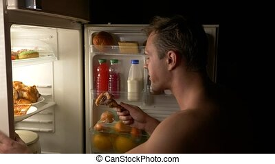 A young muscular man opens the refrigerator at night. night hunger. diet. gluttony,
