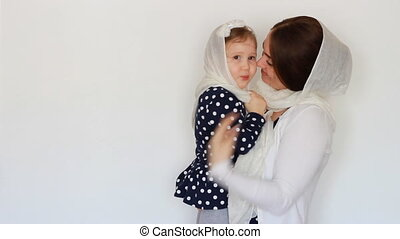 A young Muslim woman in a hijab holds a child in her arms....