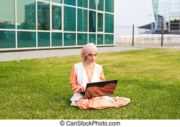 A young muslim woman using laptop outdoors