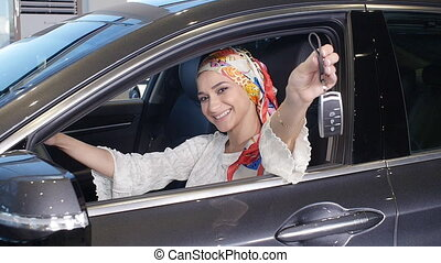 A young Muslim woman with keys from a new car