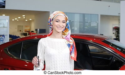 A young Muslim woman with keys from a new car - a young...