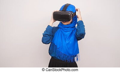 A young Muslim woman with virtual reality glasses