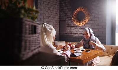 A young muslim women sitting and talking in modern cafe. Mid...