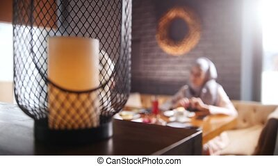 A young muslim women sitting in a cafe and talking. A modern...