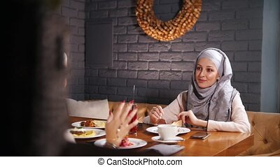 A young muslim women sitting in a cafe, talking and...