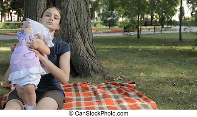 A young nanny putting a baby girl down on a blanket. The baby girl creeps away