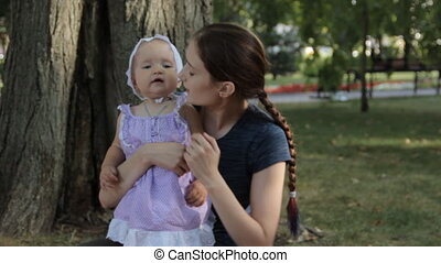 A young nanny touching a baby girl s nose. The baby girl rubs her nose