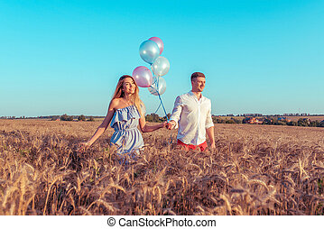A young pair of lovers, a man and a girl are walking along a wheat field in summer. In hands of holding colorful balloons. Concept walk after a holiday party on weekend, fun event smile and joy.