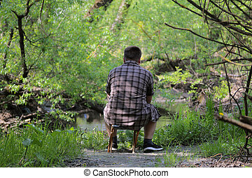 A young plump man sits on a small folding chair with his back to the camera. Sitting on the banks of the river watching the water. In the park among the bright green foliage.