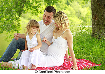 young pregnant family on nature