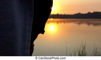 a Young Pregnant Woman Does a Yoga Exercise on a Lake Bank at Sunset