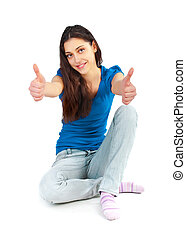 A young pretty girl sitting on the floor with thumbs up