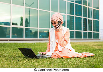 A young pretty muslim businesswoman in a park while talking on smartphone looking at the laptop