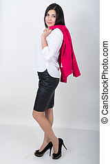 A young pretty slim asian woman standing in a leather skirt and white blouse. holding a red jacket on shoulderl