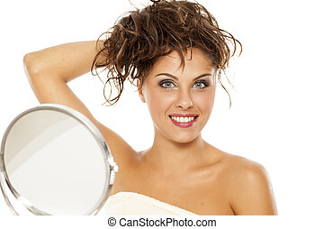 A young, pretty woman holds her hair