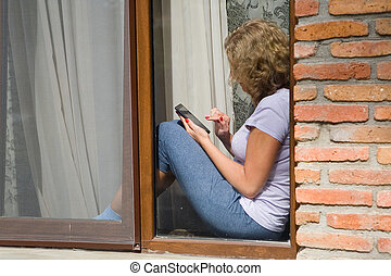 A young pretty woman is sitting on the windowsill and holding a phone in her hand.