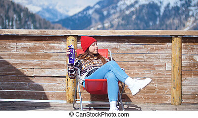A young pretty woman sitting in the lounger on a background of mountains with bottle of water