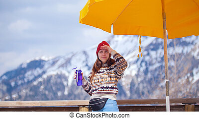 A young pretty woman standing on a background of mountains with water bottle and looks into the distance