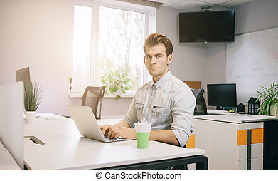The young guy is sitting at the computer in the office with the windows behind his back