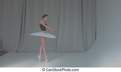 A young promising ballerina is dancing a classical ballet. ...