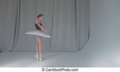 A young promising ballerina is dancing a classical ballet. White background and bright lighting in the studio