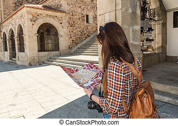 A young red-haired tourist with a backpack consults a map in the main square of Caceres, next to the old town.
