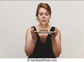 A young red-haired woman in a smart black dress holds a cake with candles and blows it out, on a white background. monochrome photo