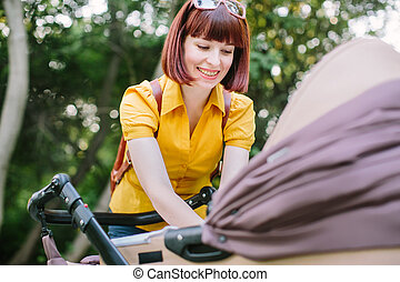 A young red-haired woman in a yellow shirt is walking with a small baby in a stroller on a summer bright day in the park