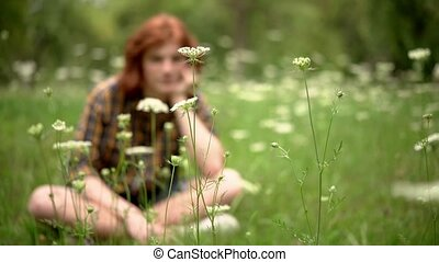 A Young Redhead Guy Sits on a Lawn in a Garden with Wildflowers.